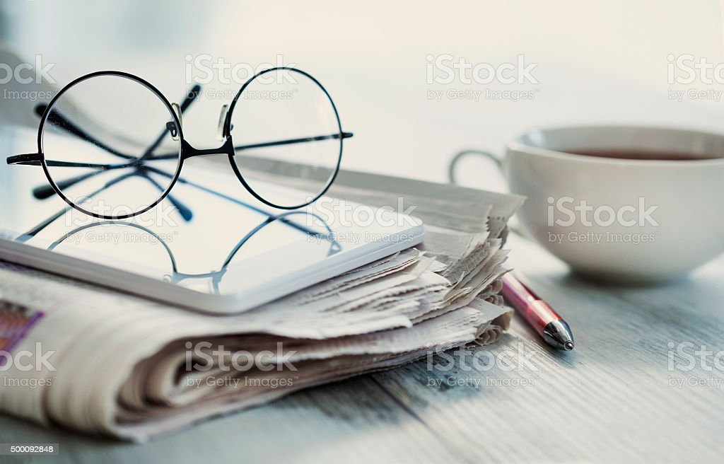 Stack of newspapers, eyeglasses on table stock photo