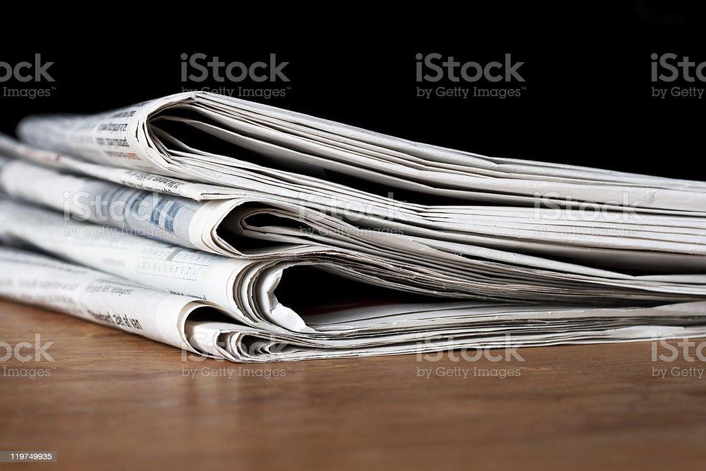 Stack of newspapers on a wooden surface royalty-free stock photo