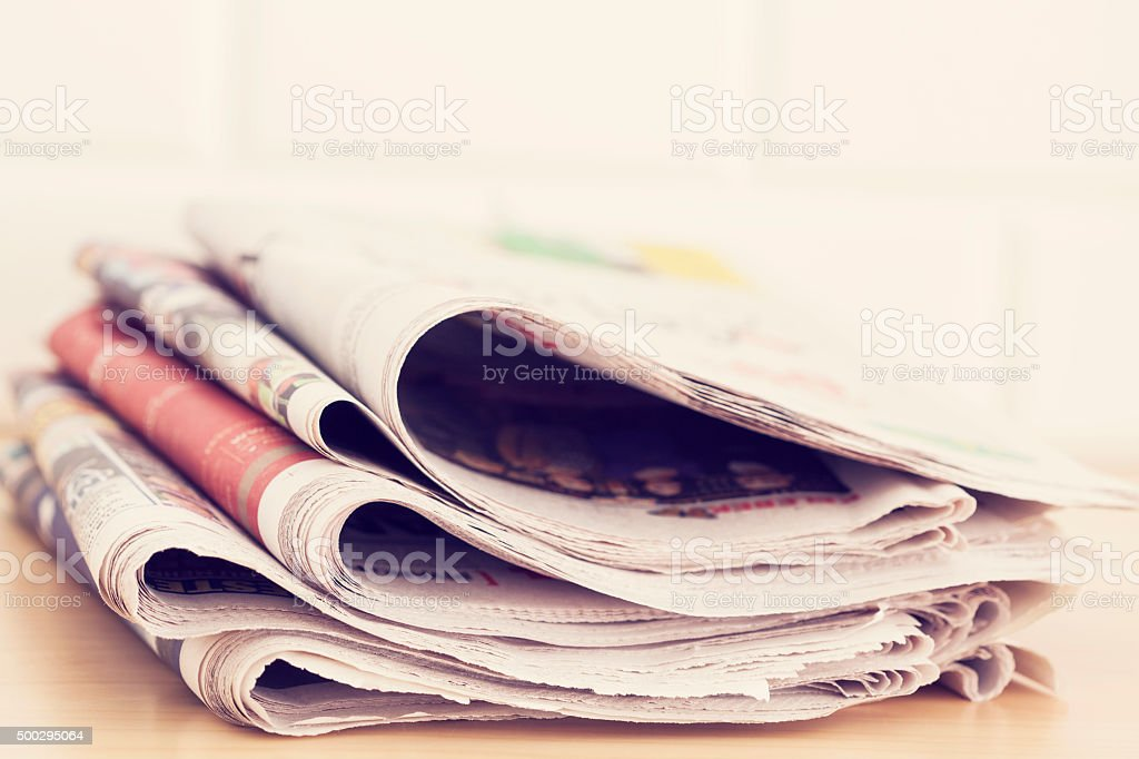 Stack of newspapers on table stock photo