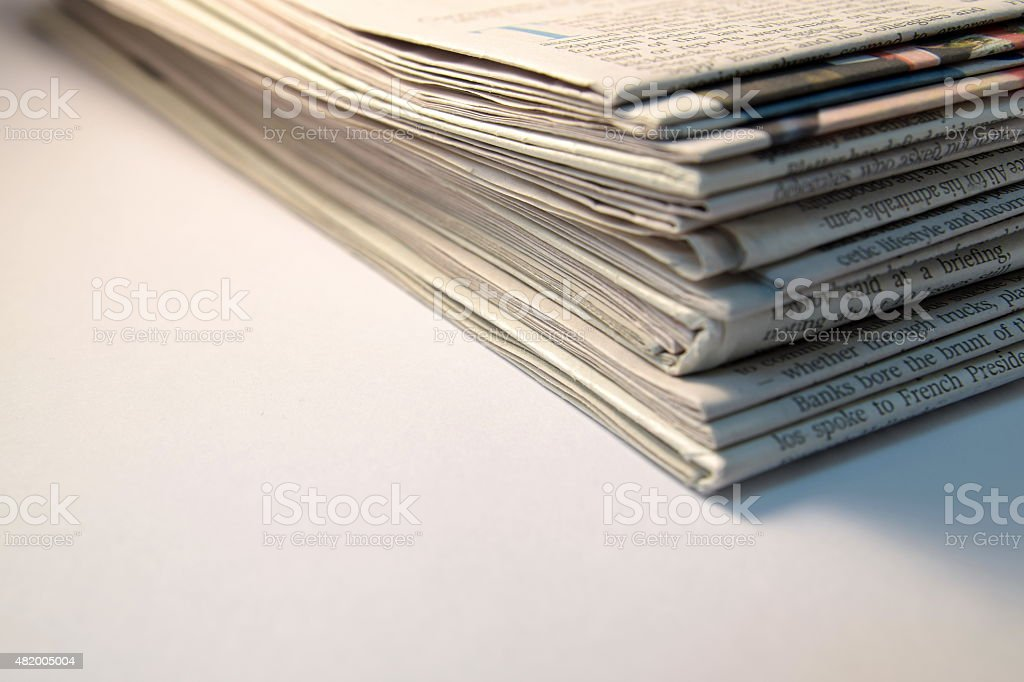 Stack of newspapers on white background stock photo