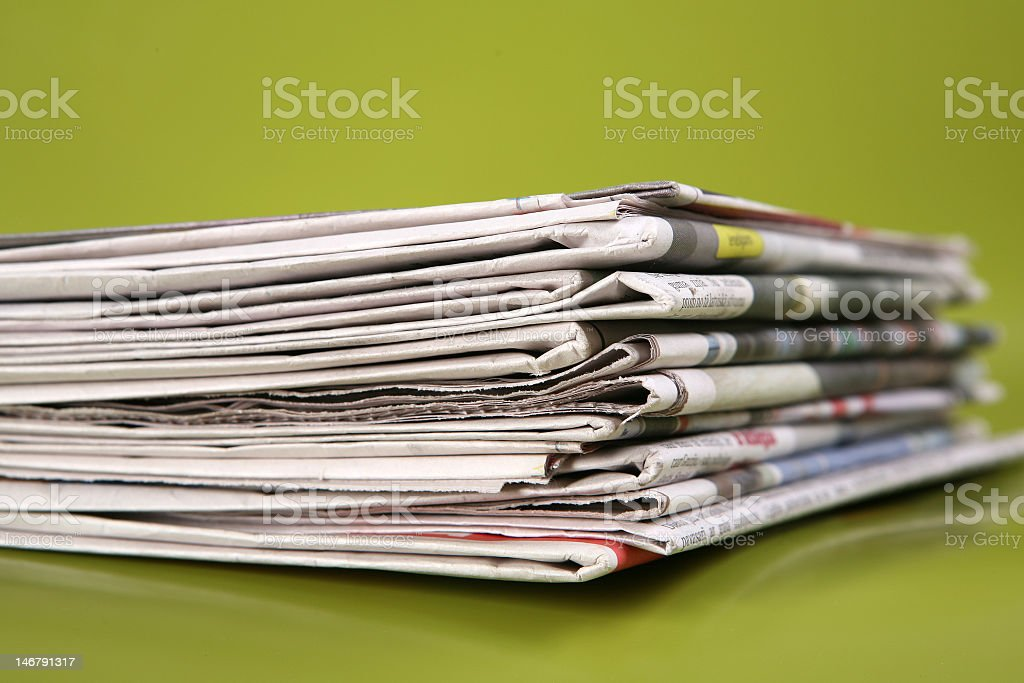 Stack of newspapers with a green background royalty-free stock photo