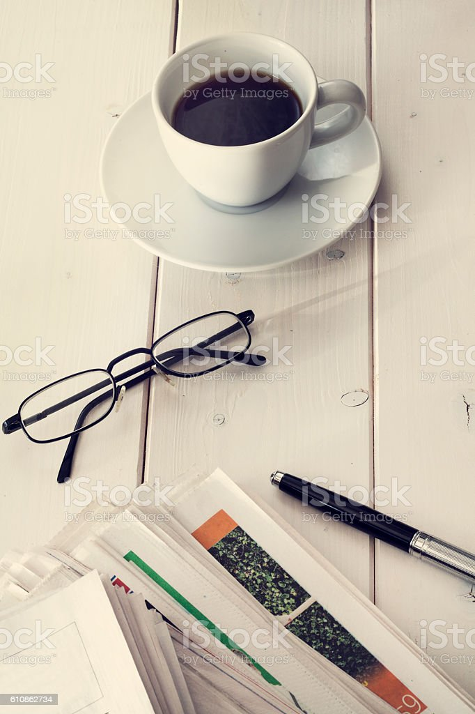 Stack of newspapers with eyeglassesand coffee stock photo