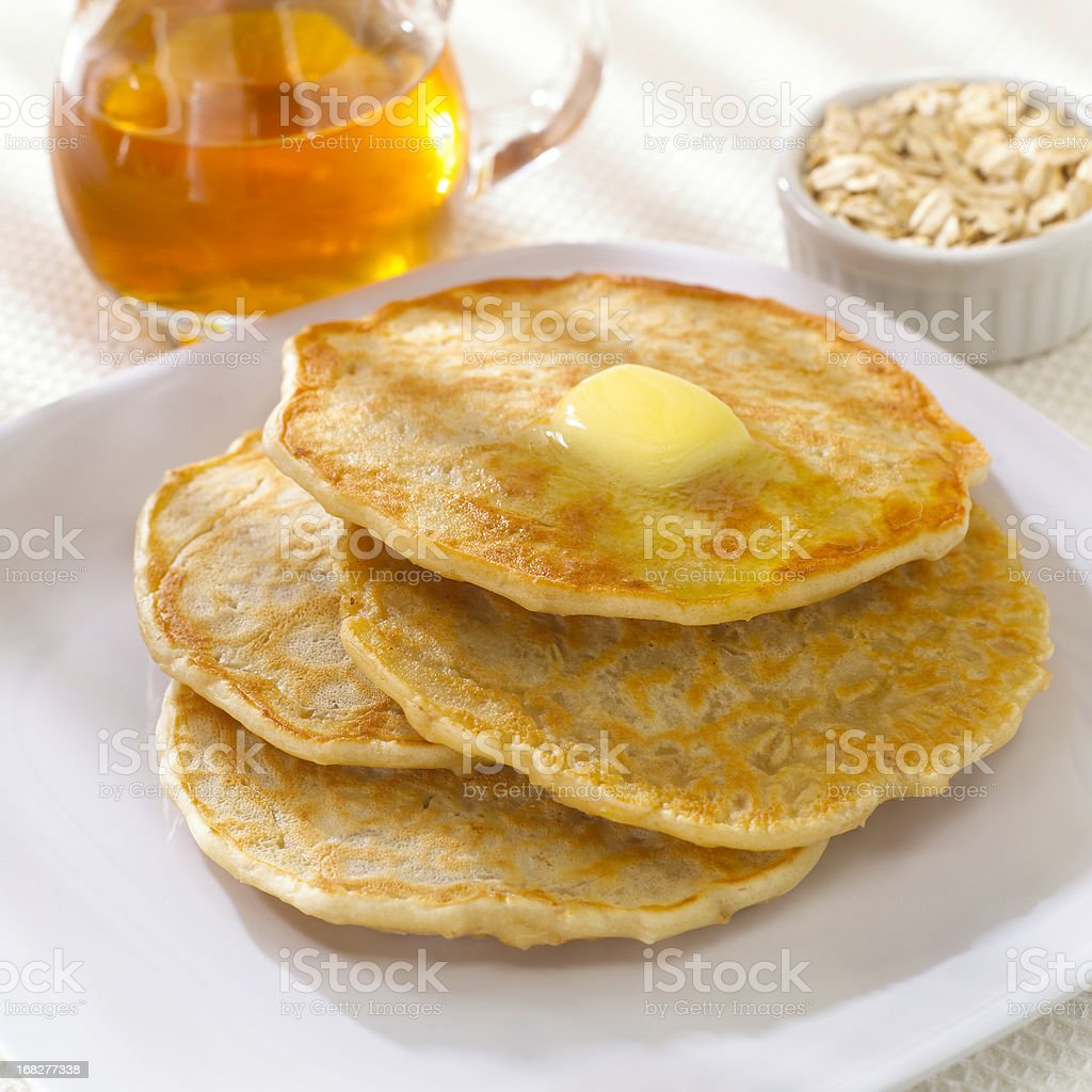 Stack of oatmeal pancakes with butter & syrup stock photo
