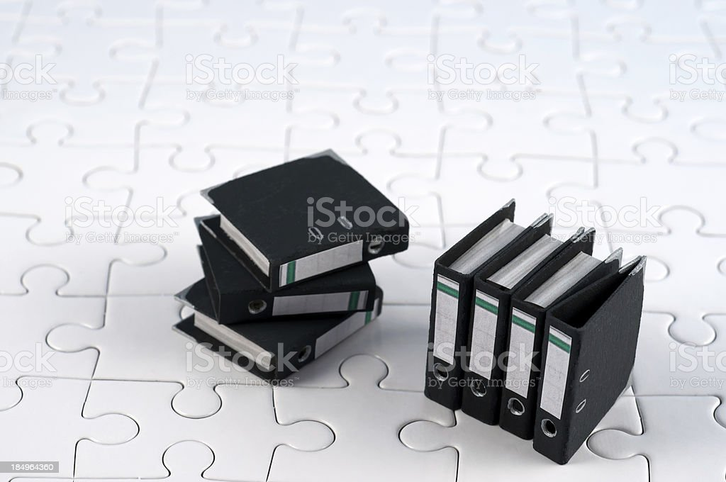 stack of office folders - ring binders on jigsaw pieces stock photo
