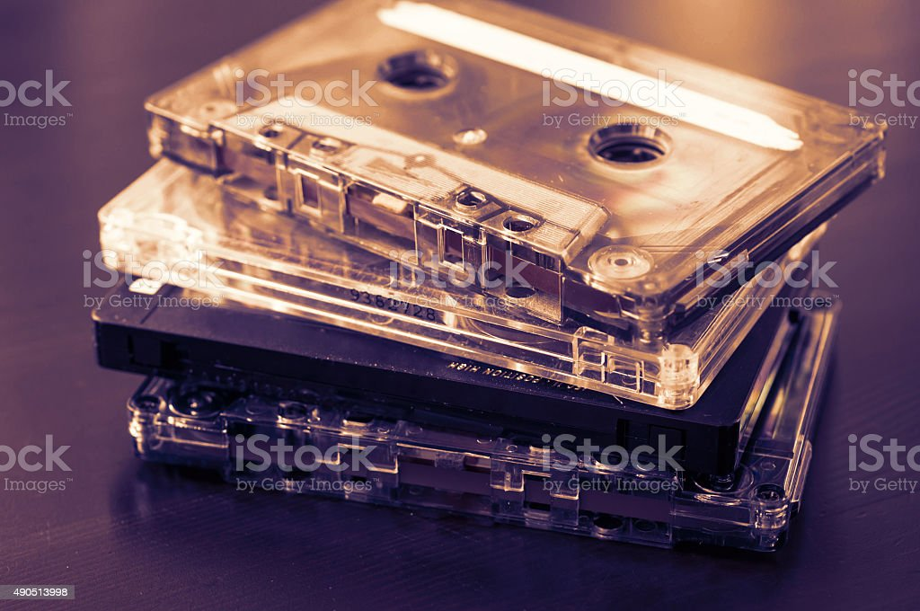 Stack of old audio tapes on a dark wooden background stock photo