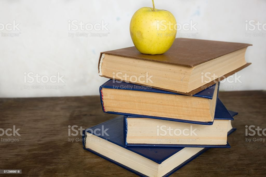 Stack of old big books and apple stock photo
