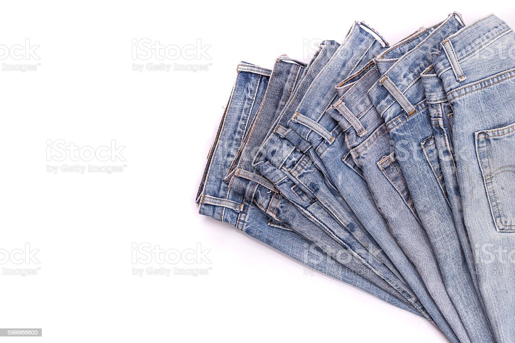 Stack of old blue jeans isolated on white stock photo