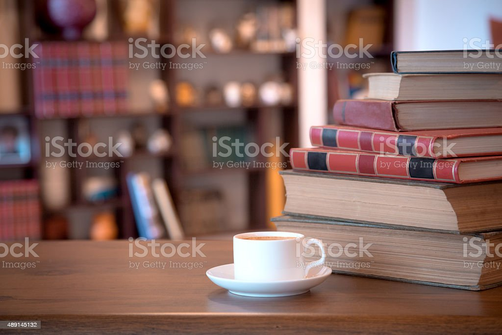 Stack of old books and cup with coffee stock photo