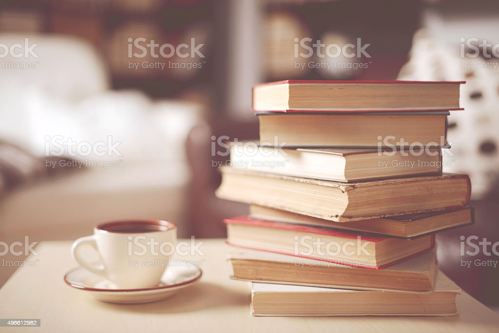 stack of old books in home interior stock photo