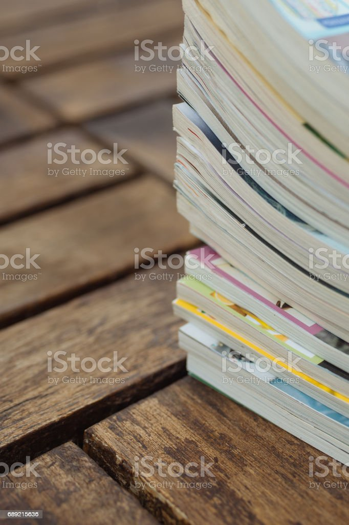 Stack of old magazines on wooden background stock photo