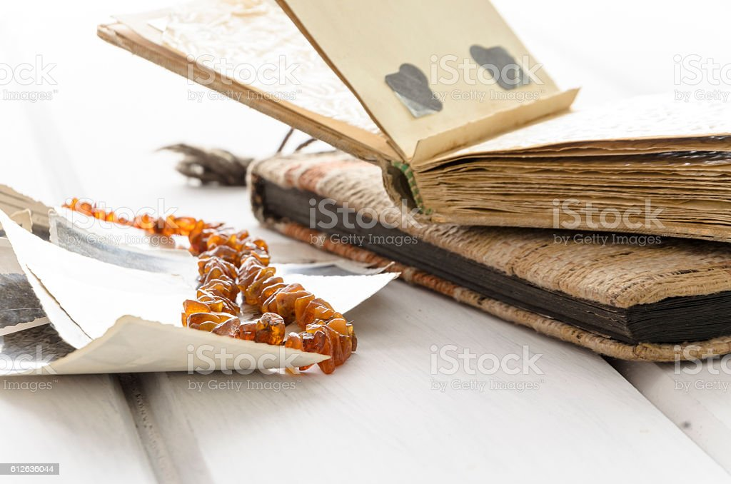 Stack of old photographs with amber necklace stock photo