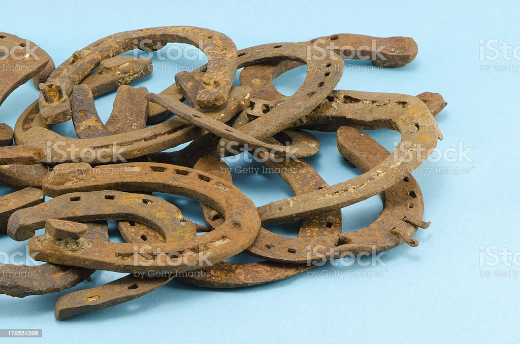 stack of old retro horse shoes on blue royalty-free stock photo