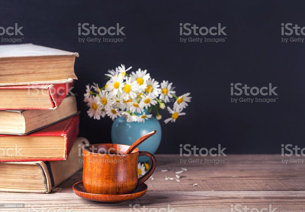 stack of old vintage books lying on a wooden table stock photo