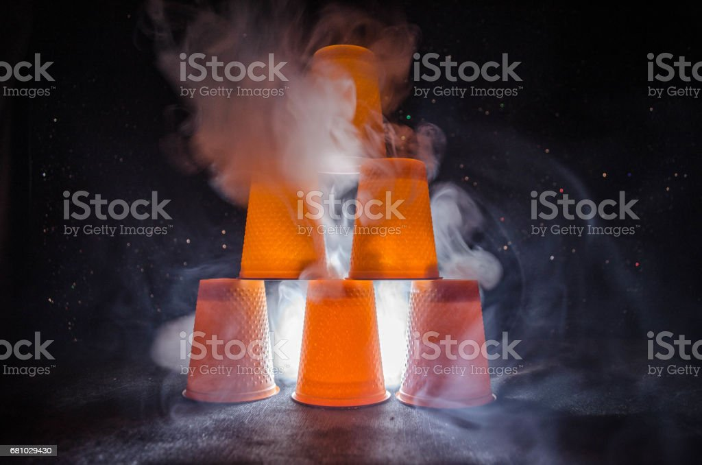 Stack of orange plastic cups with straw on dark background stock photo