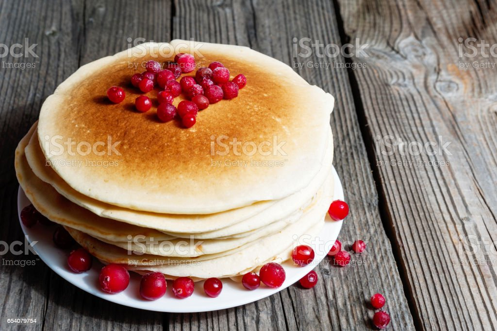 A stack of pancakes with cranberries on a white plate on a wooden boards background stock photo