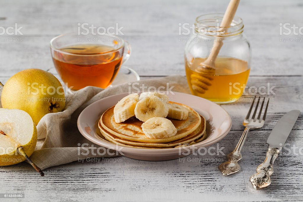 Stack of pancakes with honey syrup and butter stock photo