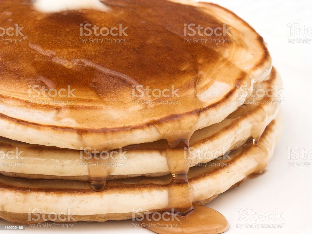 A stack of pancakes with maple syrup flowing on the sides  stock photo