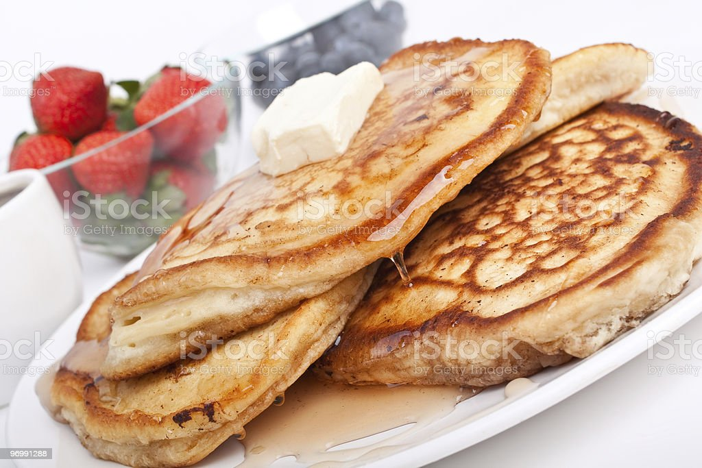 stack of pancakes with syrup and fruit stock photo