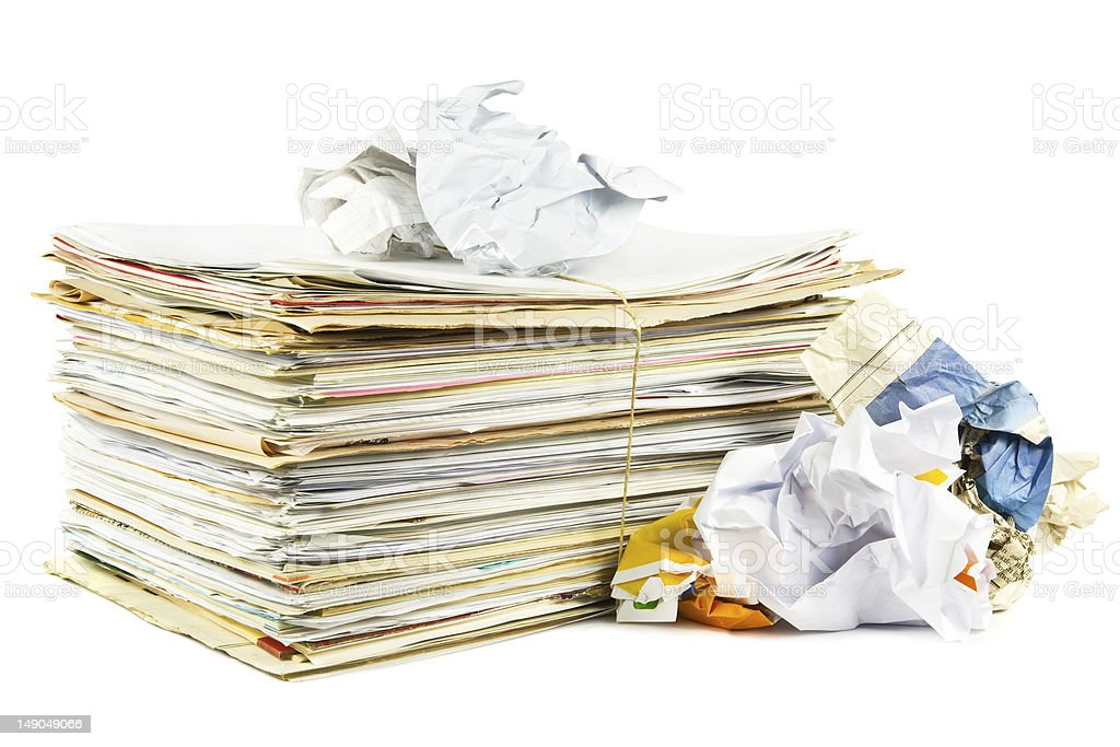 A stack of paper beside crumpled papers stock photo