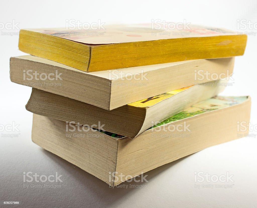 Stack of paperback books with shadow on white,  copy space stock photo
