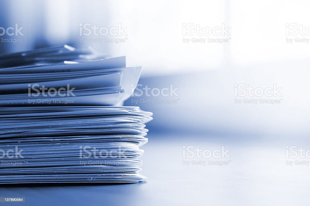 Stack of papers with blue tint stock photo