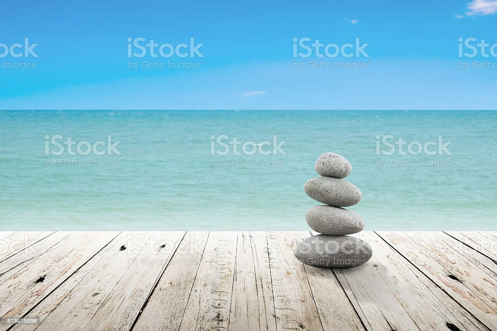 Stack of pebble stones at the beach on a wooden. stock photo