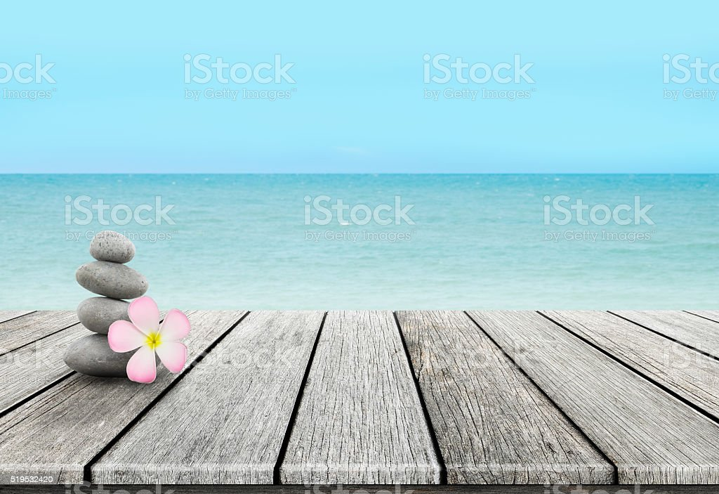 Stack of pebble stones at the beach on a wooden stock photo