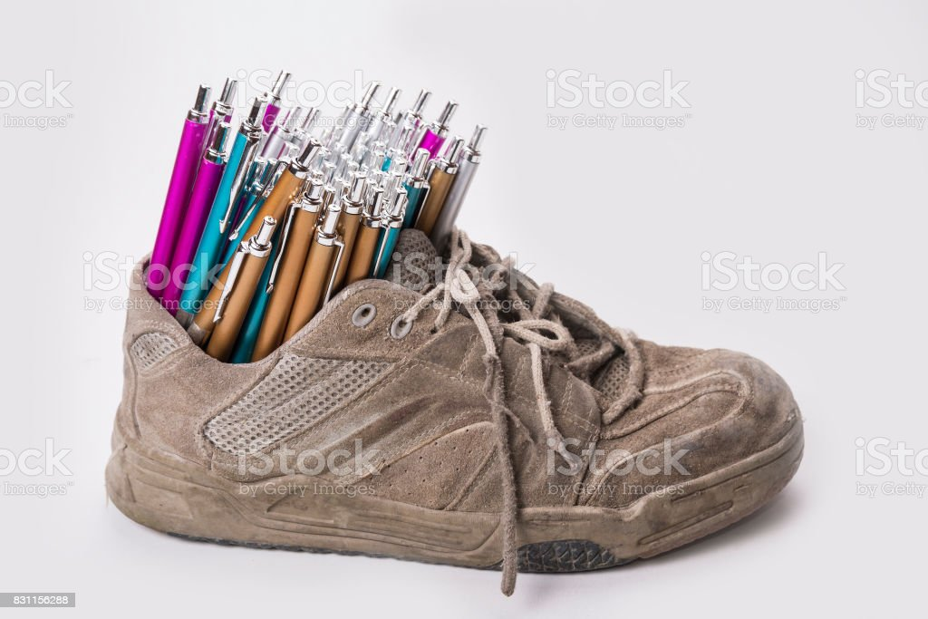 Stack of pens inserted to the old  wear out sneaker stock photo