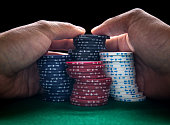 Stack of poker chips and two hands on green table.