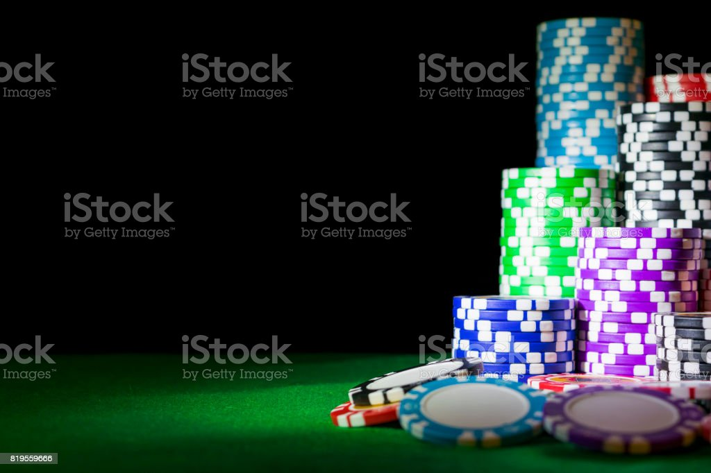 Stack of Poker chips on a green gaming poker table at the casino....