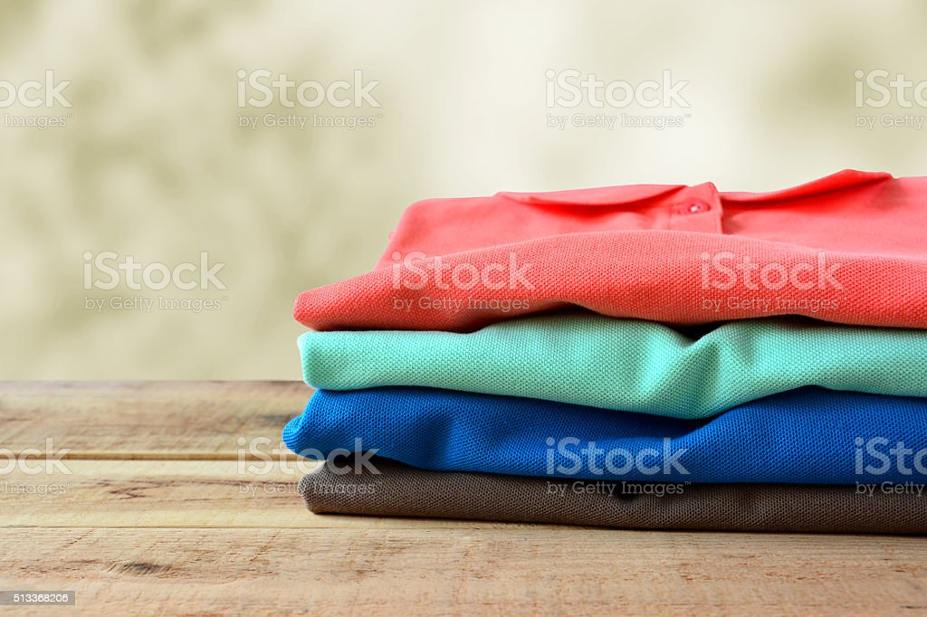 Stack of polo shirt on wooden. stock photo