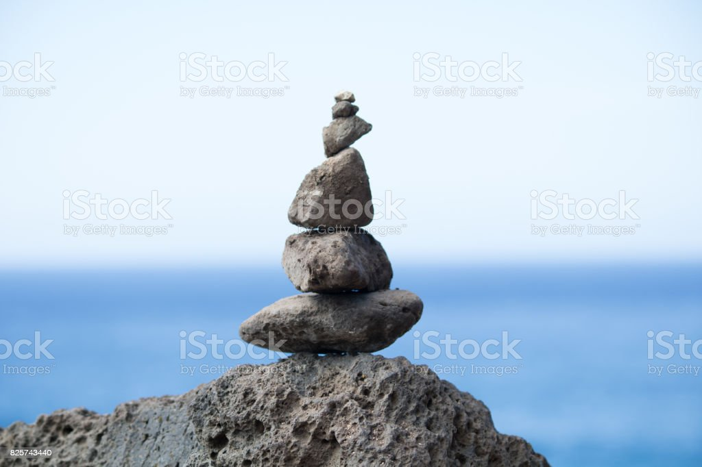 A stack of rocks with blue ocean background stock photo