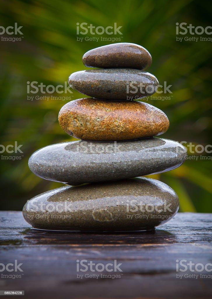 stack of round smooth wet pebbles stock photo