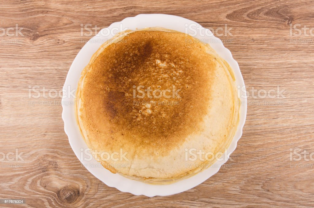 Stack of russian pancakes in white dish on wooden table stock photo