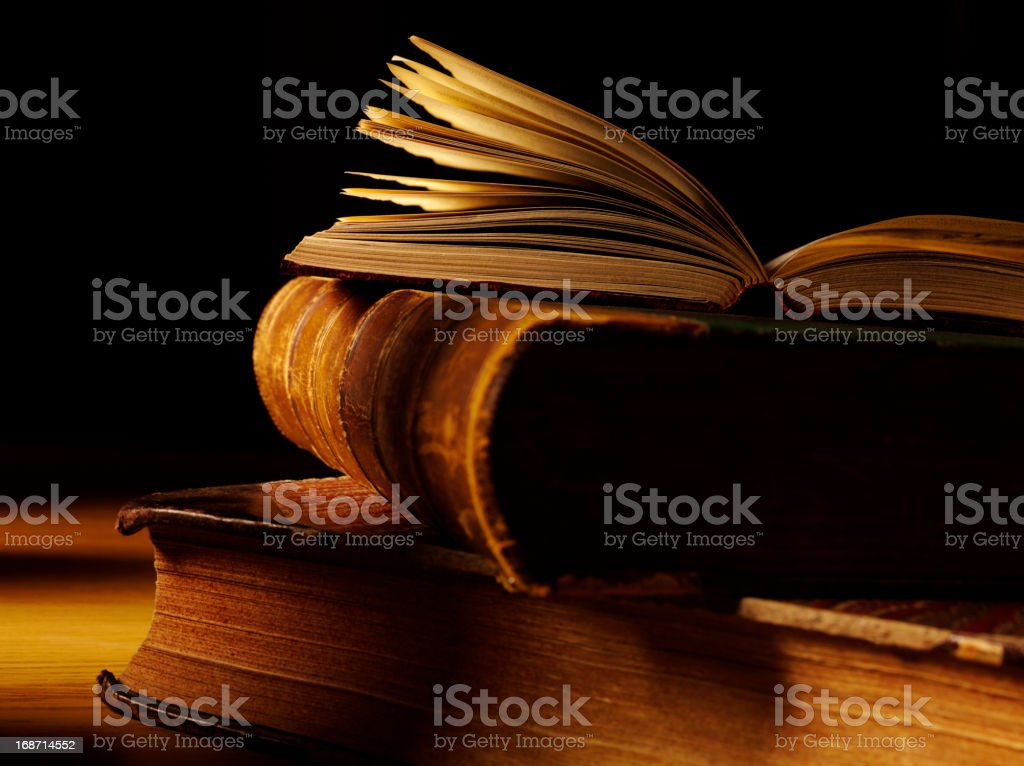 Stack of rustic, antique books on dark background royalty-free stock photo