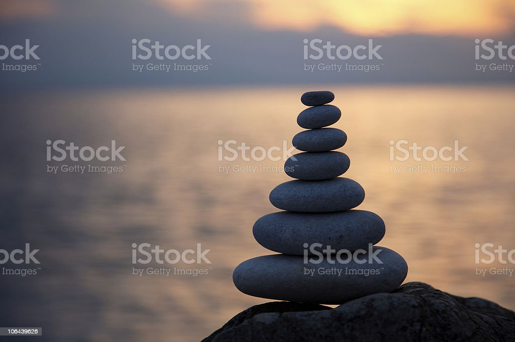 Stack of seven pebbles at sunset stock photo