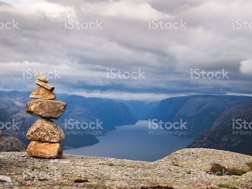 Stack of six rocks on top of a cliff with landscape view stock photo