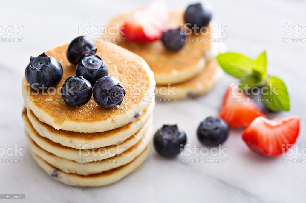 Stack of small pancakes with berries stock photo