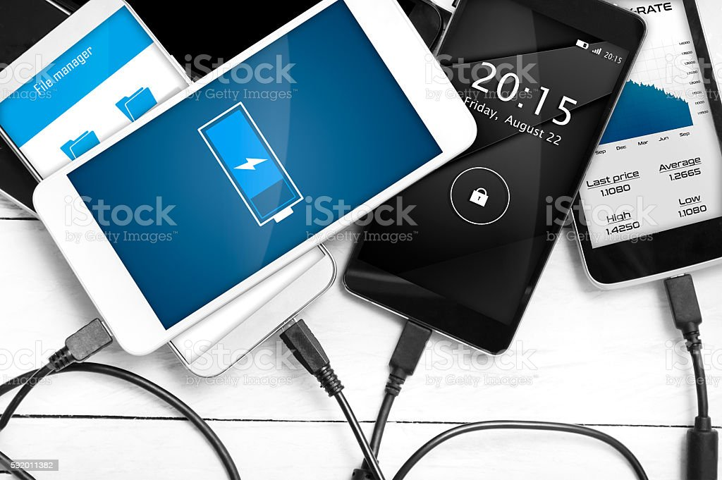 Stack of smartphones connected to power source. stock photo