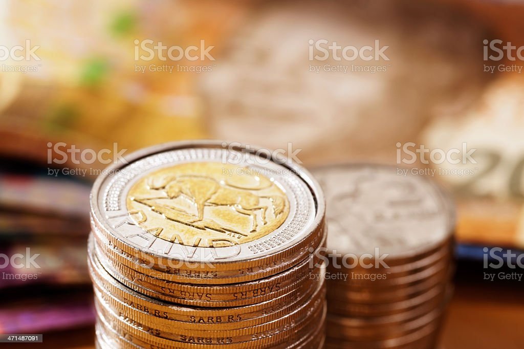 Stack of South African Five Rand coins with banknotes behind stock photo