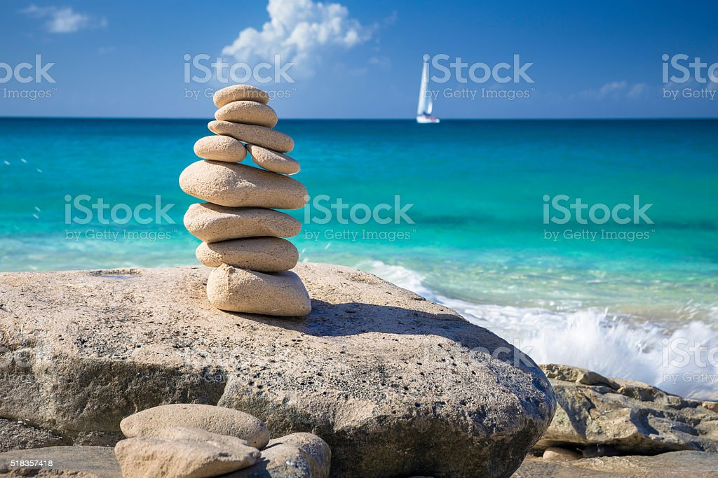 Stack of stones at beach with yacht on a background stock photo