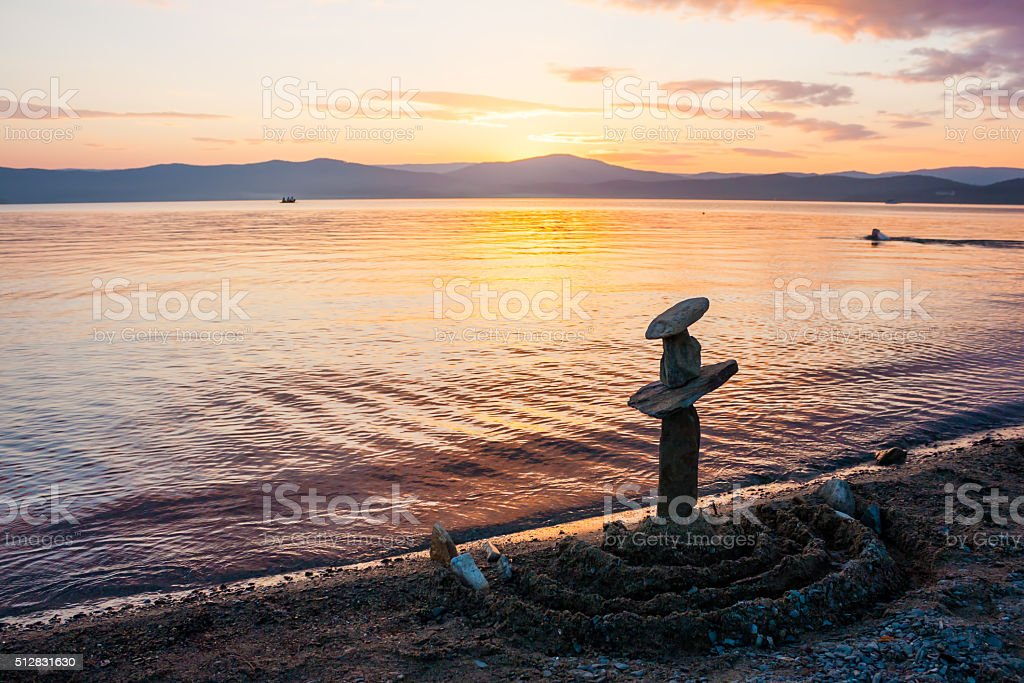Stack of stones on the beach at sunset skyline royalty-free stock photo