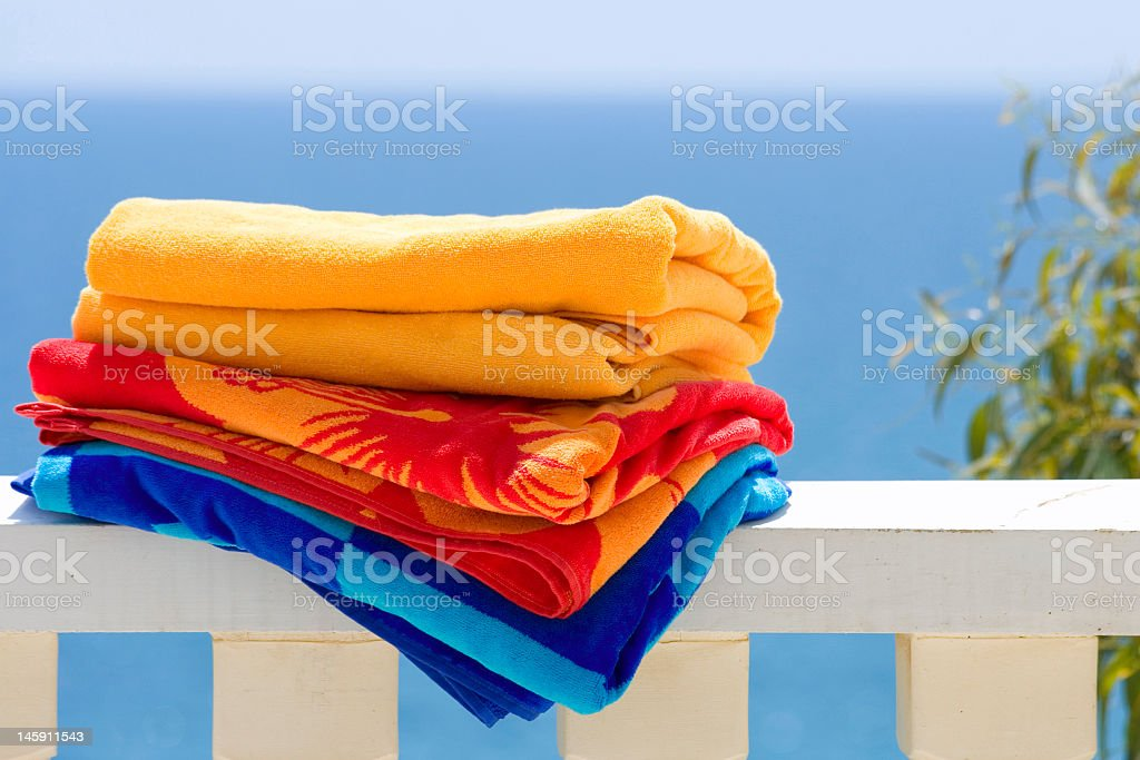 Stack of summer beach towels on white porch fence royalty-free stock photo