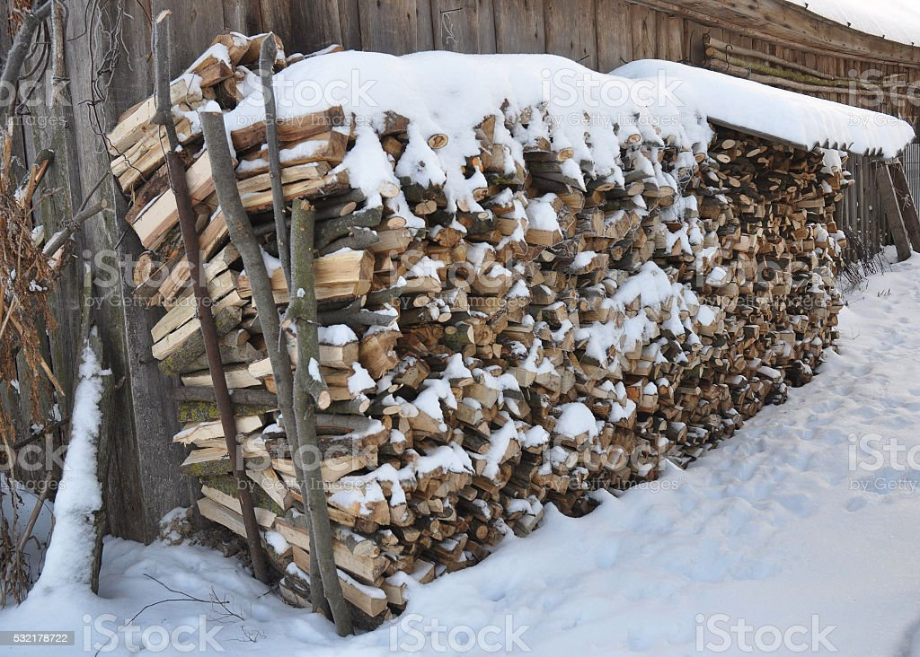 stack of the snowy firewood on old wooden barn background stock photo