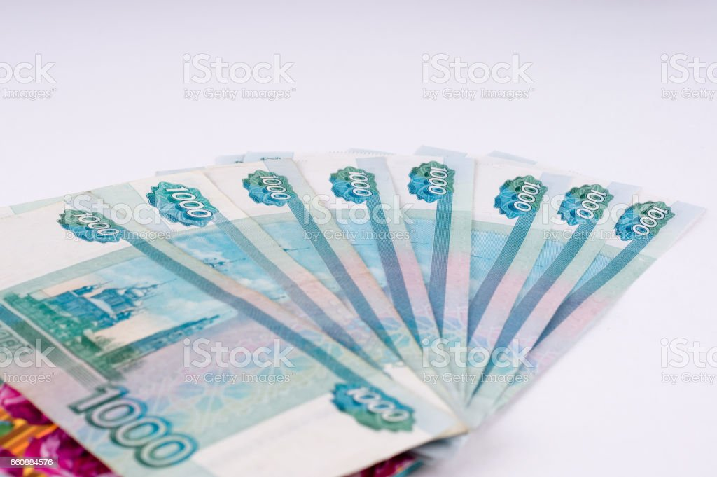 A stack of thousand-ruble banknotes, spread out and an envelope for money. Russian currency on a white background. stock photo