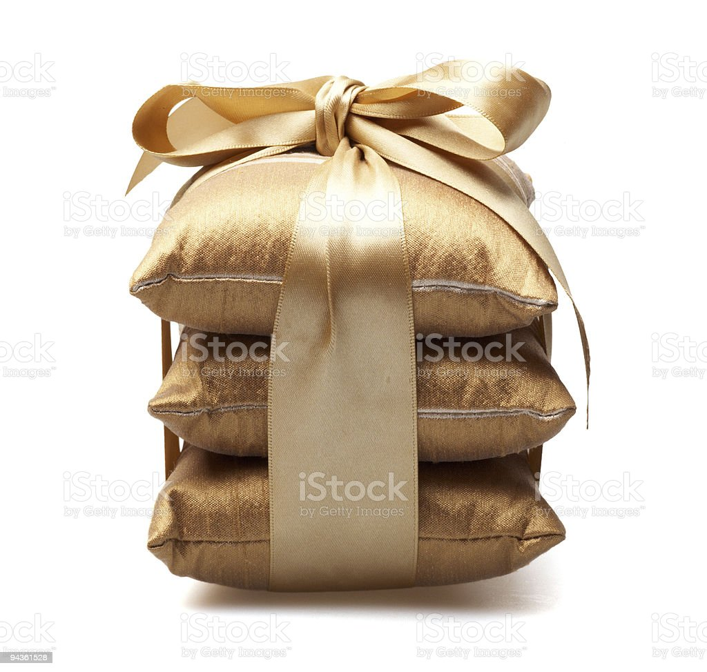 Stack of three golden colored pillows tied with gold ribbon royalty-free stock photo