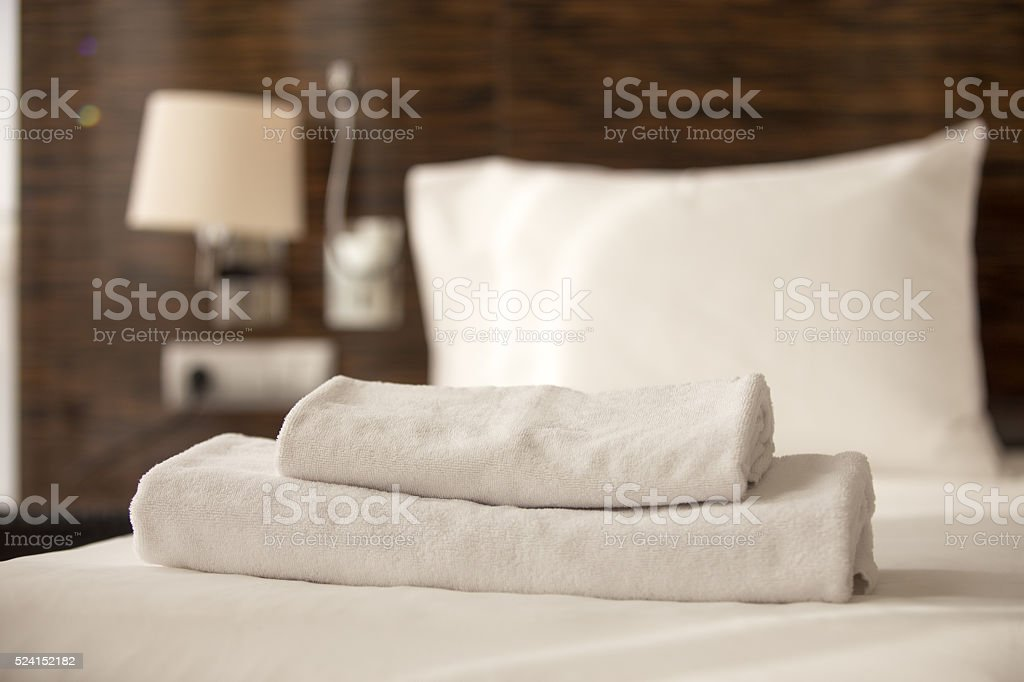 Stack of towels on the bed stock photo