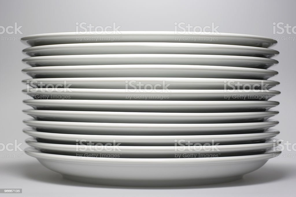 Stack of twelve white plates viewed from side on white stock photo
