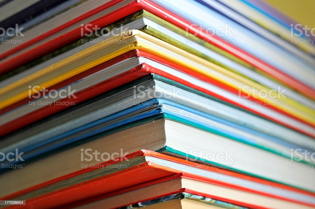 Stack of various colored and sized books stock photo