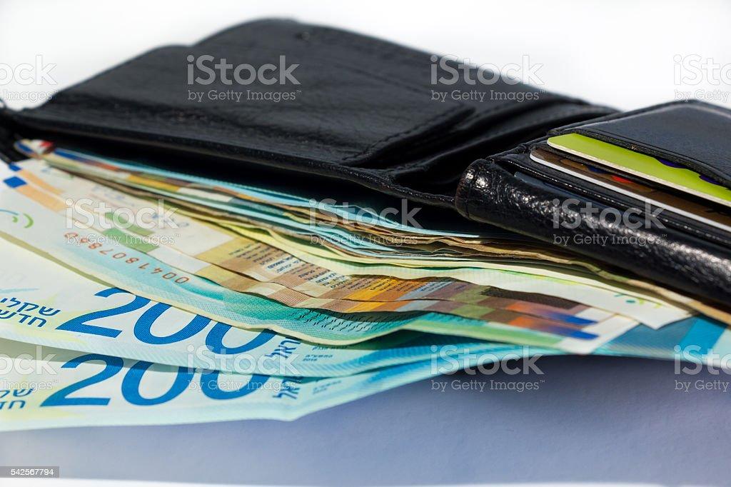 Stack of various of israeli shekel money bills in open black leather...